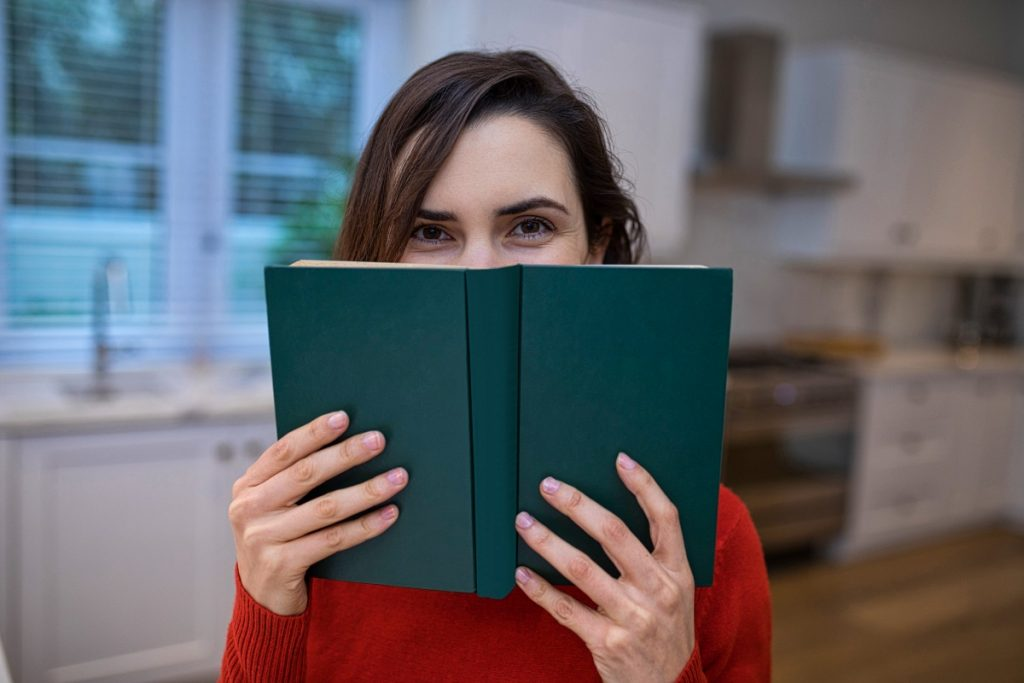 Portrait Of Beautiful Woman Covering Her Face With Book